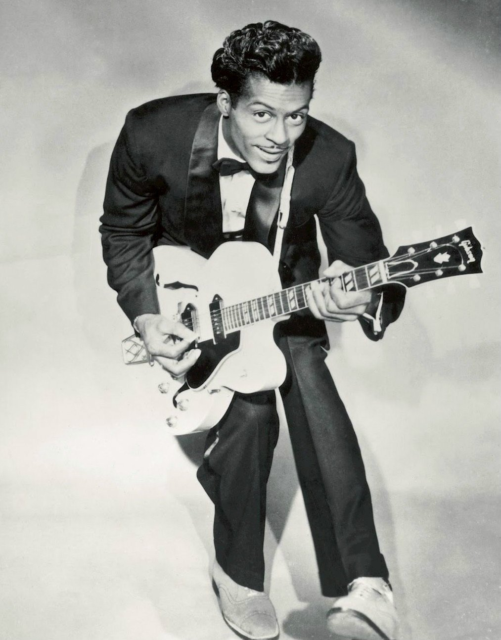Chuck Berry stooping for his duck walk, one of the greatest guitar players who brought rock n roll to the masses