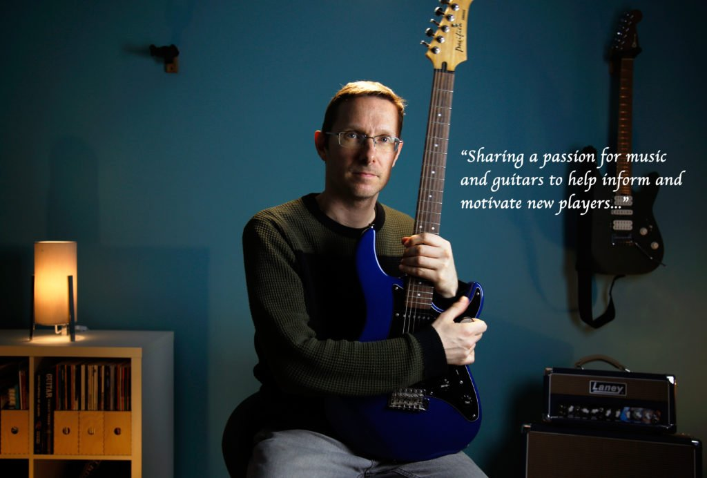 Founder of Tunelectric, Rob Cox holding a guitar